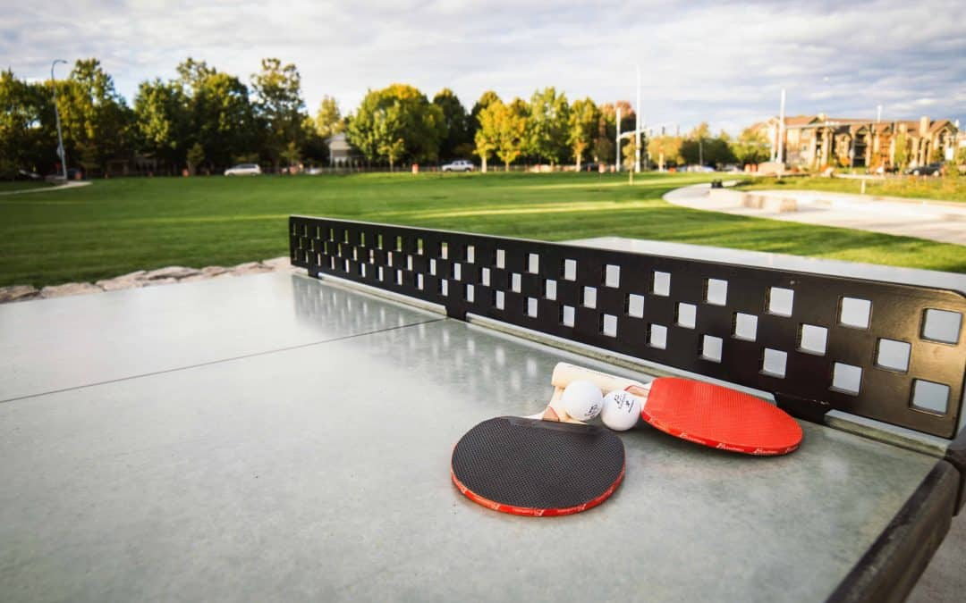 Concrete ping pong table with paddles on top outside at a public park