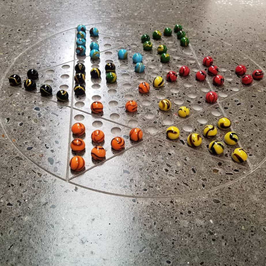Outdoor Chinese Checkers board with marbles mid game.